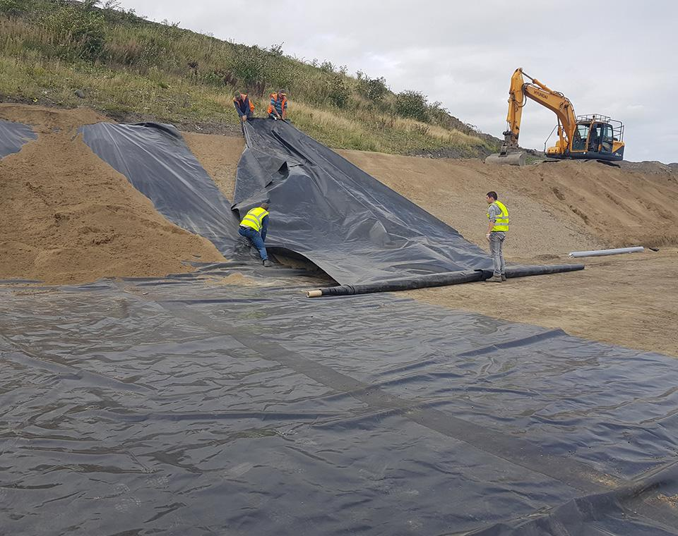 men covering ground with large plastic covers